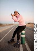 Купить «Young woman applies make up while standing on rollerblades.», фото № 14442027, снято 20 декабря 2013 г. (c) age Fotostock / Фотобанк Лори