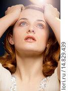 Купить «Young Woman with Hands on Head Looking Up», фото № 14829439, снято 17 февраля 2012 г. (c) age Fotostock / Фотобанк Лори