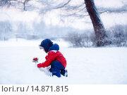 Купить «Маленький мальчик сажает волшебную ветку в снег», фото № 14871815, снято 18 октября 2018 г. (c) Ирина Мойсеева / Фотобанк Лори