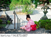 Купить «Little Japanese girl wearing a traditional kimono waits at the Kiyomizu-dera Temple classified as a UNESCO World Heritage by UNESCO.», фото № 14873687, снято 17 июля 2013 г. (c) age Fotostock / Фотобанк Лори