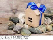 Купить «Бумажный домик перевязанный синим бантом на дощатом фоне», фото № 14883727, снято 30 ноября 2015 г. (c) Наталья Осипова / Фотобанк Лори