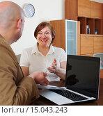 Мужчина сидит за столом перед ноутбуком и смотрит на пожилую веселую женщину, которая что-то спрашивает или объясняет. Стоковое фото, фотограф Оксана Лозинская / Фотобанк Лори