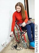 Женщина, сидящая в инвалидном кресле, думает как дотянуться до электрической розетки. Стоковое фото, фотограф Кекяляйнен Андрей / Фотобанк Лори