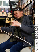 Купить «Music instrument store owner in Shanghai, China plays Erhu Chinese fiddle.», фото № 15505591, снято 29 октября 2014 г. (c) age Fotostock / Фотобанк Лори