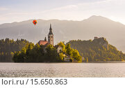 Купить «Catholic Church in Bled Lake and Bled Castle, Slovenia with Hot Air Balloon Flying at Sunrise», фото № 15650863, снято 20 июня 2019 г. (c) PantherMedia / Фотобанк Лори