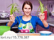Счастливая женщина на кухне с двумя пучками лука в руках. Стоковое фото, фотограф Оксана Лозинская / Фотобанк Лори