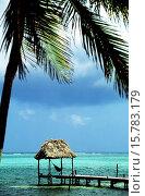 Купить «Cabana with hammock overlooking aqua tropical waters at the end of a dock, Ambergris Caye, Belize.», фото № 15783179, снято 5 апреля 2020 г. (c) age Fotostock / Фотобанк Лори
