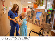 "Купить «A child life specialist at CHOC Children´s Hospital in Orange, CA,shows a ""chemo duck"" to a young girl chemotherapy cancer patient. The duck demonstrates...», фото № 15795867, снято 4 декабря 2014 г. (c) age Fotostock / Фотобанк Лори"