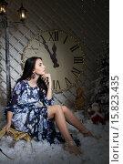 Купить «Девушка у рождественской елки на фоне большого циферблата», фото № 15823435, снято 26 ноября 2015 г. (c) Момотюк Сергей / Фотобанк Лори