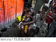 Купить «A Haitian girl bathes her baby outside a sheet-metal house in a shanty town close to La Saline market, Port-au-Prince, Haiti, 14 July 2008. Although Latin...», фото № 15836839, снято 14 июля 2007 г. (c) age Fotostock / Фотобанк Лори