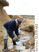 Купить «Золотоискатель промывает горную породу», фото № 15878443, снято 12 ноября 2014 г. (c) Free Wind / Фотобанк Лори