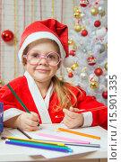 Купить «Девочка-новогодний гномик рисует открытку в подарок на рождество», фото № 15901335, снято 12 декабря 2015 г. (c) Иванов Алексей / Фотобанк Лори