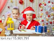 Купить «Санта-Клаус пишет поздравительное письмо, помощница-фея стоит рядом с подсвечником в руке», фото № 15901791, снято 12 декабря 2015 г. (c) Иванов Алексей / Фотобанк Лори