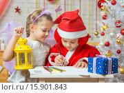 Купить «Санта-Клаус пишет поздравительное письмо, помощница-фея стоит рядом, подняв в руке подсвечник», фото № 15901843, снято 12 декабря 2015 г. (c) Иванов Алексей / Фотобанк Лори