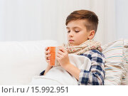 Купить «ill boy with flu in scarf drinking tea at home», фото № 15992951, снято 6 ноября 2015 г. (c) Syda Productions / Фотобанк Лори