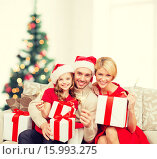 Купить «smiling family holding gift boxes and sparkles», фото № 15993275, снято 26 октября 2013 г. (c) Syda Productions / Фотобанк Лори