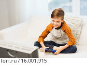 Купить «happy boy with joystick playing video game at home», фото № 16001915, снято 24 октября 2015 г. (c) Syda Productions / Фотобанк Лори