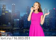 Купить «happy young woman with party horn over night city», фото № 16003051, снято 31 октября 2015 г. (c) Syda Productions / Фотобанк Лори