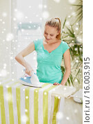 Купить «happy woman with iron and ironing board at home», фото № 16003915, снято 25 января 2015 г. (c) Syda Productions / Фотобанк Лори