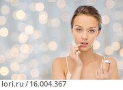 Купить «young woman applying lip balm to her lips», фото № 16004367, снято 31 октября 2015 г. (c) Syda Productions / Фотобанк Лори