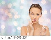 Купить «young woman applying lip balm to her lips», фото № 16005331, снято 31 октября 2015 г. (c) Syda Productions / Фотобанк Лори