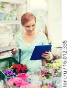 Купить «woman with tablet pc and basket at flower shop», фото № 16012335, снято 25 февраля 2015 г. (c) Syda Productions / Фотобанк Лори