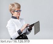 Купить «Пожилая женщина нажимает на тачскрин планшета, серый фон», фото № 16126919, снято 13 декабря 2015 г. (c) Кекяляйнен Андрей / Фотобанк Лори