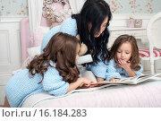 Семья на кровати перед рождественским венком читает книгу. Стоковое фото, фотограф Nataliya Pogodina / Фотобанк Лори