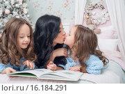 Семья на кровати перед елкой читает книгу, мама целует дочку. Стоковое фото, фотограф Nataliya Pogodina / Фотобанк Лори