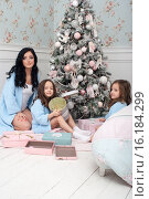 Семья в одинаковой одежде перед елкой разбирают подарки. Стоковое фото, фотограф Nataliya Pogodina / Фотобанк Лори