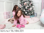 Семья из двух сестер  возле елки среди подарков. Стоковое фото, фотограф Nataliya Pogodina / Фотобанк Лори