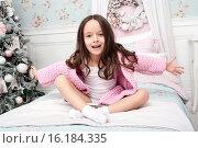 Маленькая красивая девочка в розовом вязаном кардигане веселится на кровати в своей спальне, рядом елка. Стоковое фото, фотограф Nataliya Pogodina / Фотобанк Лори