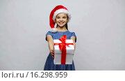 Купить «happy smiling girl in santa hat holding gift box», видеоролик № 16298959, снято 12 декабря 2015 г. (c) Syda Productions / Фотобанк Лори