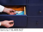 Человек скрывает банконты евро в ящик. Стоковое фото, фотограф Виктор Колдунов / Фотобанк Лори