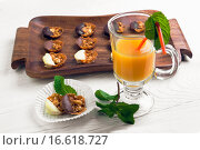 Домашние конфеты на деревянном подносе  и бокал с апельсиновым соком на столе. Стоковое фото, фотограф Sergey Fatin / Фотобанк Лори