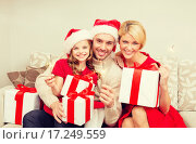 Купить «smiling family holding gift boxes and sparkles», фото № 17249559, снято 26 октября 2013 г. (c) Syda Productions / Фотобанк Лори