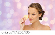 Купить «young woman cleaning face with exfoliating sponge», фото № 17250135, снято 31 октября 2015 г. (c) Syda Productions / Фотобанк Лори