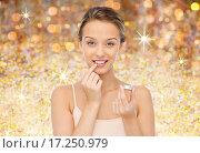 Купить «smiling young woman applying lip balm to her lips», фото № 17250979, снято 31 октября 2015 г. (c) Syda Productions / Фотобанк Лори
