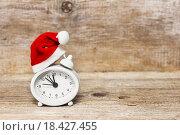 Купить «В ожидании Нового года. Будильник в шапке Санты на деревянном столе», фото № 18427455, снято 1 января 2016 г. (c) Наталья Осипова / Фотобанк Лори