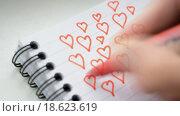 Купить «Человек рисует сердечки в тетради», видеоролик № 18623619, снято 3 декабря 2015 г. (c) Валерий Гусак / Фотобанк Лори