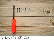 Купить «Крестовая отвертка и шурупы на деревянном фоне», фото № 18931035, снято 19 июля 2018 г. (c) Зезелина Марина / Фотобанк Лори