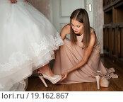 Купить «Подружка помогает одеть туфли невесте», эксклюзивное фото № 19162867, снято 13 сентября 2015 г. (c) Игорь Низов / Фотобанк Лори