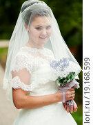 Купить «Портрет счастливой невесты накрытой фатой с цветами в руках», эксклюзивное фото № 19168599, снято 13 сентября 2015 г. (c) Игорь Низов / Фотобанк Лори