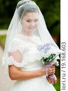 Купить «Портрет счастливой невесты накрытой фатой с цветами в руках на прогулке», эксклюзивное фото № 19168603, снято 13 сентября 2015 г. (c) Игорь Низов / Фотобанк Лори