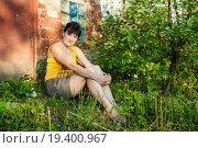 Купить «Грустная женщина среднего возраста сидит возле кирпичного дома», эксклюзивное фото № 19400967, снято 25 июля 2015 г. (c) Игорь Низов / Фотобанк Лори