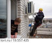 Купить «Промышленный альпинист устанавливает кондиционер на стену многоэтажного дома», эксклюзивное фото № 19557435, снято 25 декабря 2015 г. (c) Вячеслав Палес / Фотобанк Лори