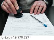 Купить «Парень ставит печать на документе, сидя за чёрным столом», эксклюзивное фото № 19970727, снято 10 января 2016 г. (c) Игорь Низов / Фотобанк Лори