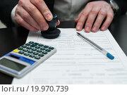 Бизнесмен ставит печать на документах в офисе. Стоковое фото, фотограф Игорь Низов / Фотобанк Лори