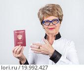 Купить «Улыбающаяся пожилая женщина показывает рукой на российский заграничный паспорт», фото № 19992427, снято 13 декабря 2015 г. (c) Кекяляйнен Андрей / Фотобанк Лори