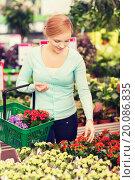 Купить «happy woman with shopping basket choosing flowers», фото № 20086835, снято 25 февраля 2015 г. (c) Syda Productions / Фотобанк Лори